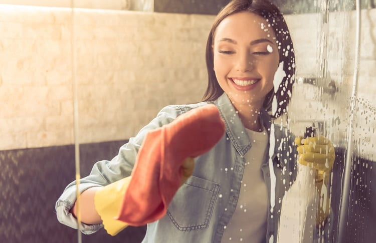 woman cleaning shower door with vinegar