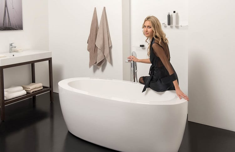 woman sitting on acrylic bathtub