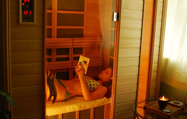 woman reading a book in infrared sauna